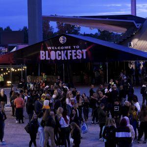 """Ett stort tält med texten """"välkommen till blockfest"""" funkar som entré till festivalen. Framför tältet syns stora klungor med festivalbesökare."""