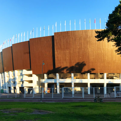 En sida av Olympiastadion med blå himmel.