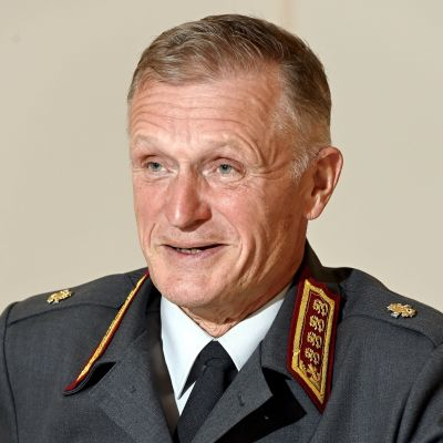 En äldre man i militäruniform tittar åt sidan och ler. Han pratar samtidigt. Han är fotograferad framför en beige vägg.