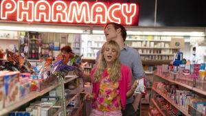 Cassandra (Carey Mulligan) och Ryan (Bo Burnham) sjunger bland hyllorna i ett apotek.  en nattklubb.