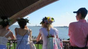 Kvinnor med blomsterkransar på huvudet tittar ut över midsommarfirande och frihetsstatyn i New York.