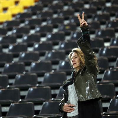 En kvinna gör fredstecknet på Dortmunds stadion.