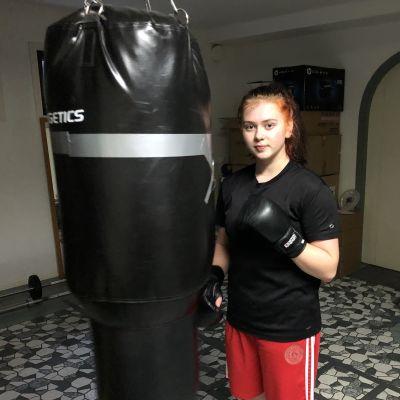 Veera Karlsson står bredvid en boxningssäck.