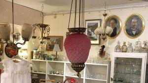 En ljusröd månskenslampa hänger i en antikaffär.