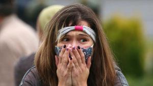 En kvinna med munskydd håller händerna för ansiktet och tittar förskräckt åt sidan.