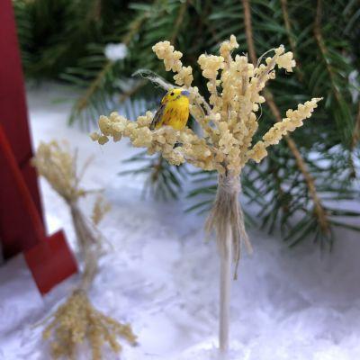 En julkärve i miniatyr i vilken det sitter en gulsparv i miniatyr.