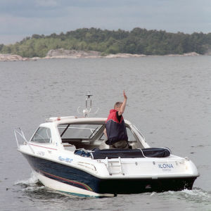 Säveltäjä Olli Kortekangas vilkuttaa moottoriveneestään rannalla oleville