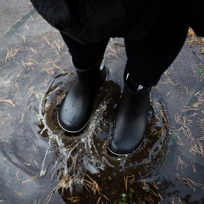 En kvinna i gummistövlar står i en vattenpöl.