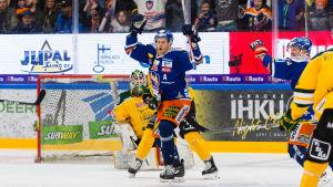 Jani Lajunen sträcker händerna i luften och firar ett mål på isen.