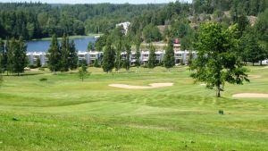 En golfplan med gröna fält, i bakgrunden syns vita radhuslängor och vatten. Solen skiner.