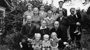 1950-luvun perhepotretti kesäisellä pihamaalla.