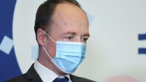 En medelåldersman i munskydd klädd i kostym sitter och ser fundersam ut.