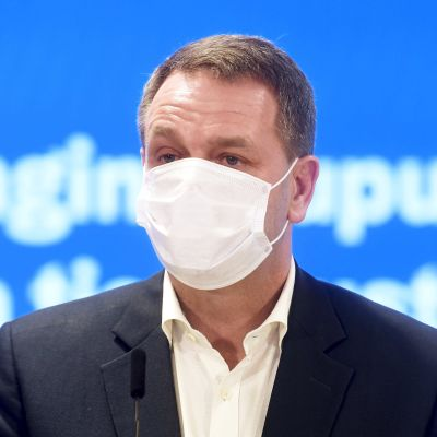 Jan Vapaavuori i munskydd på presskonferensen. Turkos bakgrund.
