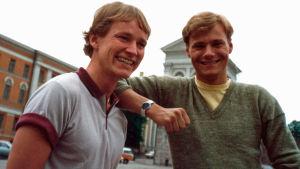 Kaksi hymyilevää nuorta miestä Helsingin Senaatintorilla