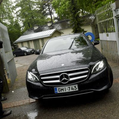 En svart bil kör ut genom grinden till statsministerns tjänstebostad Villa Bjälbo. Sannfinländarnas ordförande Jussi Halla-aho sitter i bilen.