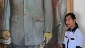 asariah Bayuni fungerar som guide i ett museum i huset där Sukarno växte upp. Hon står framför en stor målning av Sukarno.