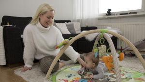 En kvinna sitter på golvet och leker med sitt spädbarn. Barnet ligger på maget på en lekmatta.