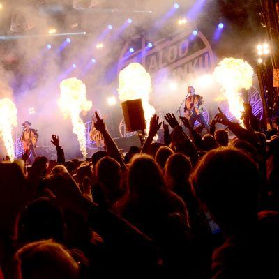 Rock-yhtye esiintyy lavalla, edessä yleisöä nauttii musiikista kädet ilmassa