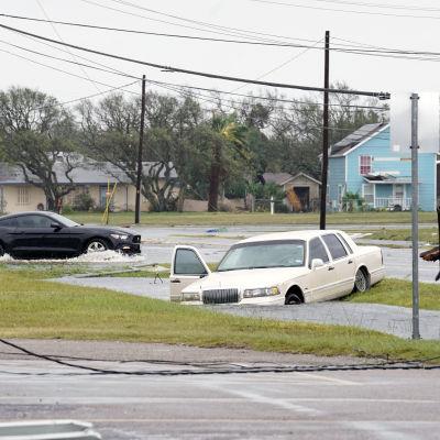 En mörk bil kör förbi en vit bil som ligger i översvämningsvatten i Rockport, Texas den 26 augusti 2017 efetr orkanen Harvey.