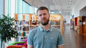 Robin Ekelund, en vit man med skägg, står i ett bibliotek.