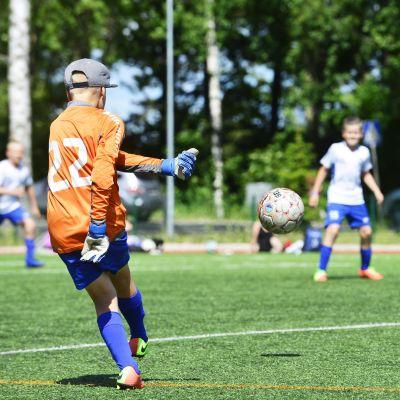 En juniormålvakt sparkar ut bollen.