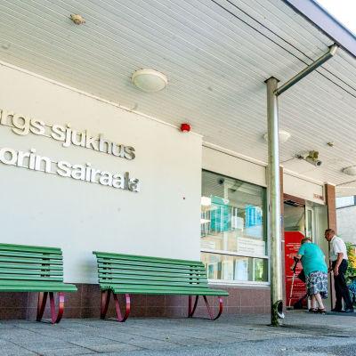 En äldre kvinna och en man påväg in i Raseborgs sjukhus. På byggnadens vägg står namnet på sjukhuset i silvriga bokstäver.