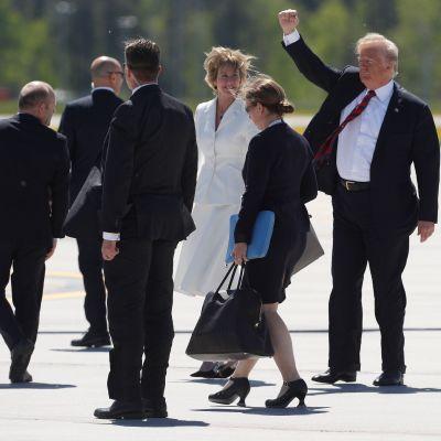Trump huvudet högre än sitt resesällskap, hälsar med knuten näve.