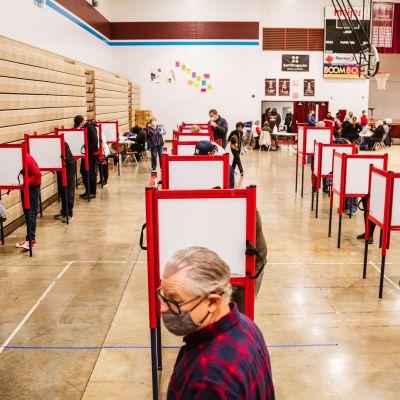 Människor röstar i röda röstningsbås.