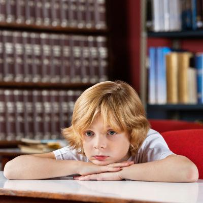 Pojke dagdrömmer och lutar huvudet mot armarna i klassrummet.