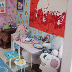 Leikkimökki, jossa pöydän ääressä istuu kaksi isoa pehmonorsua ympärillään erilaisia norsutavaroita.