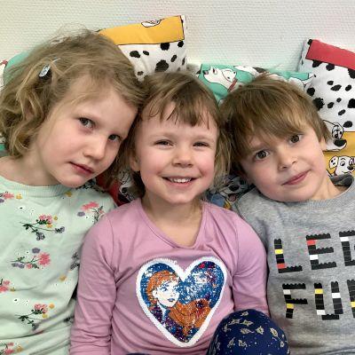 Tre barn lutar sig mot dynor.