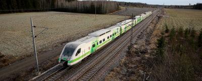 Tåg kör genom landsortslandskap