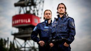 Två poliser poserar vid en lyftkran, Tomas Jalonen och Eero Tuominen.