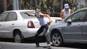 Stenkastande palestinska ungdomar inför begravning av mördad tonåring i östra Jerusalem.