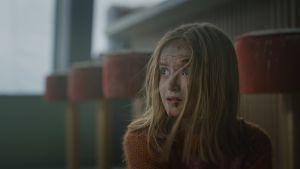 Närbild på Julia (Edith Haagenrud-Sande) som har fått sår i ansiktet av glassplitter och sitter på golvet och ser rädd ut.