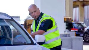 En manlig sjöbevakare står i gul väst viden en bil och pratar med någon inne i bilen.