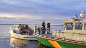 En sjöbevakningsbåt och en mindre båt ligger sida vid sida på ett nästan spegelblankt hav.