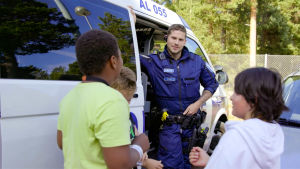 En polis och tre barn står framför en polisbil och pratar.