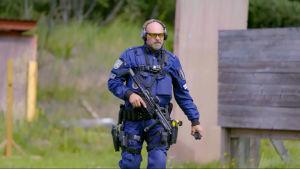 Polisen Timo promenerar över en skjutbana i full mundering.