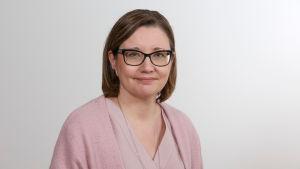 En kvinna med glasögon i rosa tröja.