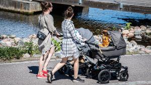 Kaksi naista lastenvaunujen kanssa kävelyllä.