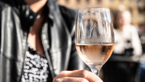 Viinilasi naisen kädessä ulkoterassilla.