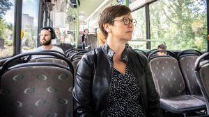 kvinna sitter i en nästan tom buss.
