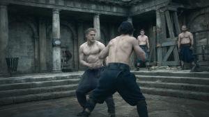 Muskulösa Arthur tränar kampsport med andra muskulösa män.
