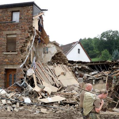 En man och en kvinna utanför ett totalförstört hus i Tyskland.