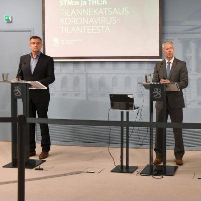 Tre tjänstemän bakom talarstolar på en presskonferens.