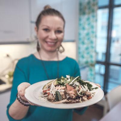 Kasvisruokaa lautasella Olivia Toivasen kädessä.