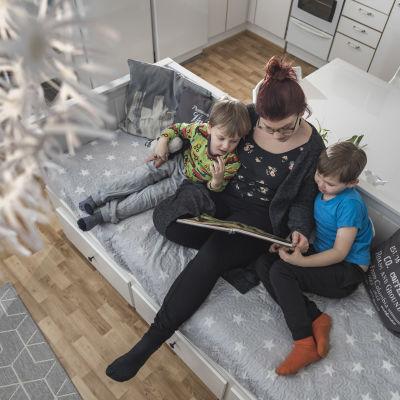 Vanhempi lukee lapsille kirjaa.