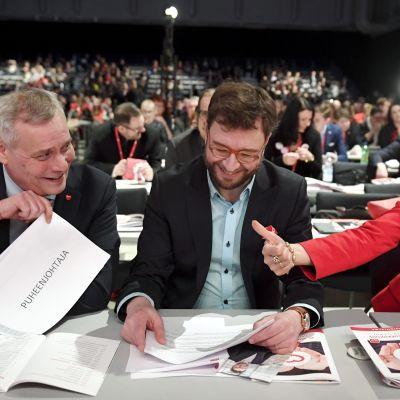 Antti Rinne, Timo Harakka och Tytti Tuppurainen sitter vid ett bord på SDP:s partikongress i Lahtis 2017. De tre kandiderar till ordförandeposten.