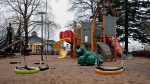 Två gungor och en klätterställning i en lekpark.